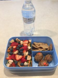 Blue lunchbox with berry salad which is made of greens, croutons, blueberries, and cut strawberries. Served with whole wheat crackers, energy balls, and water.