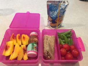 Pink lunchbox with peaches, whole wheat wrap, snap peas, and tomatoes. Drink is a Capri Sun.