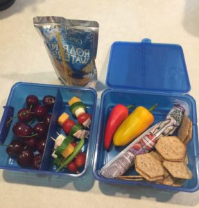 Blue lunchbox with cherries, caprese kabobs, peppers, yogurt, and whole wheat crackers. Drink is a Capri Sun.